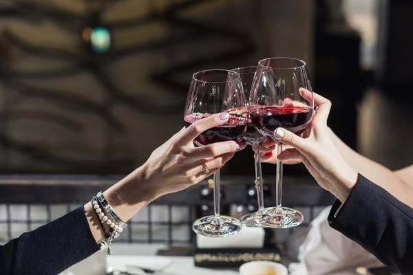 People celebrating with wine glasses at restaurant