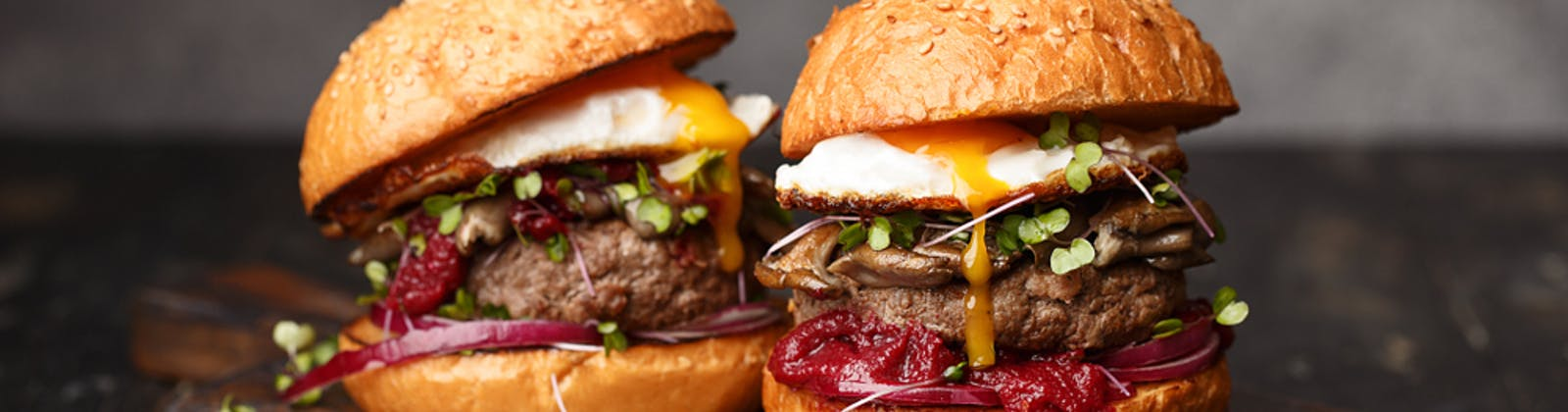 two beef burgers with egg and sauce