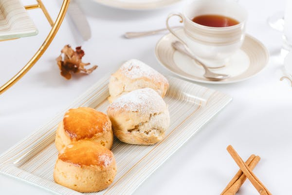 scones with tea and cinnamon sticks