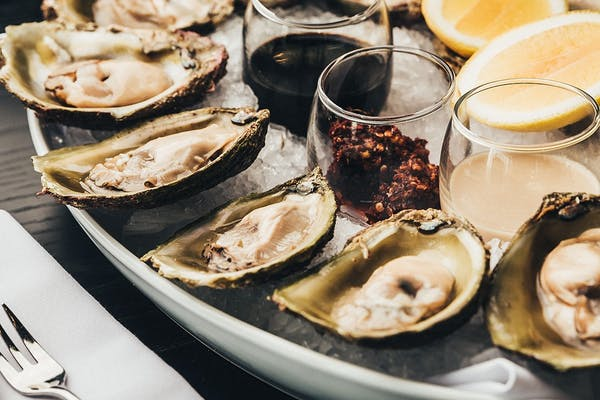 bluff oysters on ice with lemon vinegar and dressings