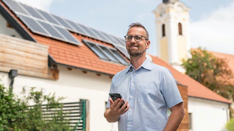 Mann mit Smartphone vor Photovoltaikanlage