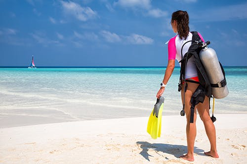 Diver standing on beach with scuba gear