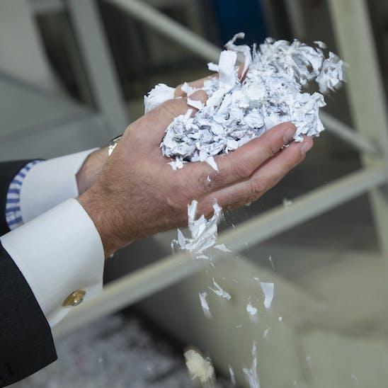 Zwei Hände gefüllt mit klein geschredderten Aktenschnipseln