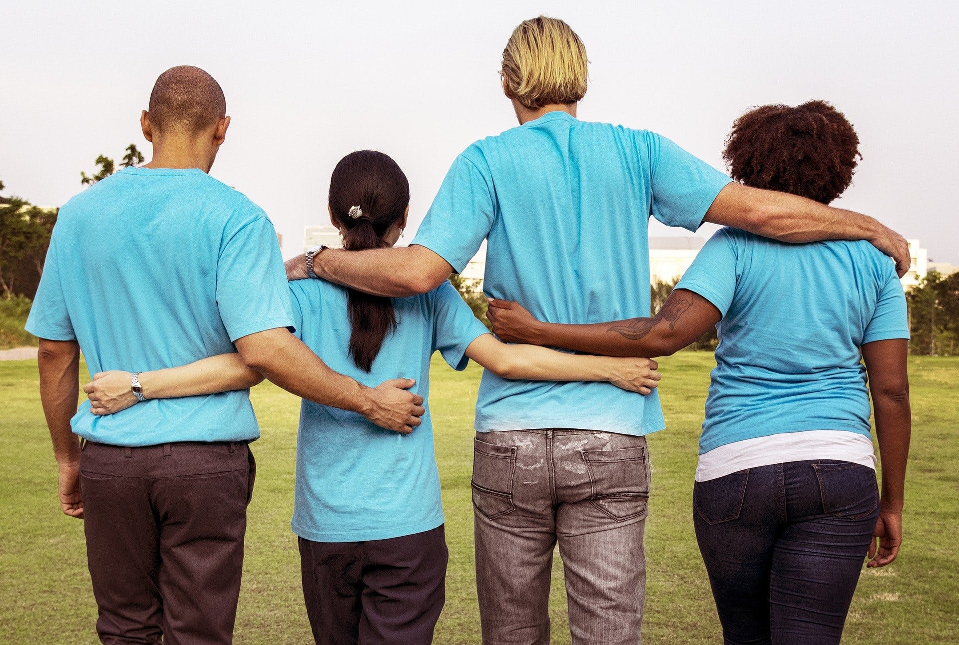 Team of four individuals side by side with arms around each other in support