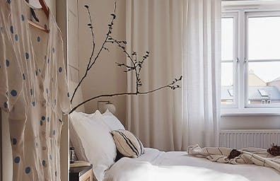 A bedroom with light voiles hanging up