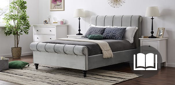 Grey velvet bed frame with grey and white bedding in a light grey bedroom. A book icon sits on the image