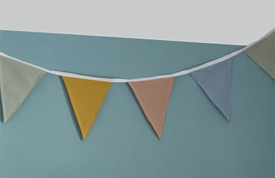 multicoloured bunting on a blue wall