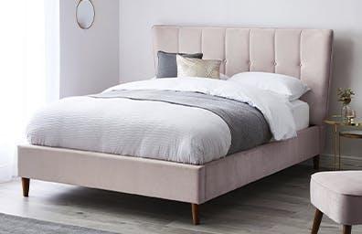 Blush pink velvet upholstered bed in a neutral room
