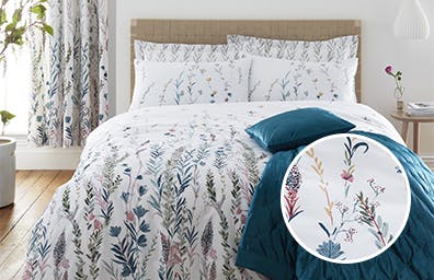 Floral duvet cover in all white room with matching curtains and a teal throw on the bed