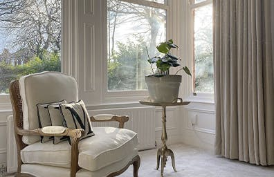 A living room with large windows and pencil pleat curtains