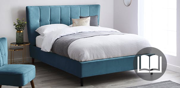 Teal coloured fabric bed with white and grey bedding. A matching chair sits in the foreground.