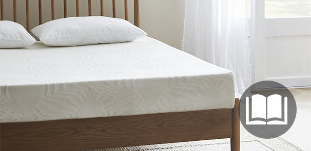 A wooden bed in a neutral bedroom holds a white mattress and 2 pillows. There is no bedding on the bed.