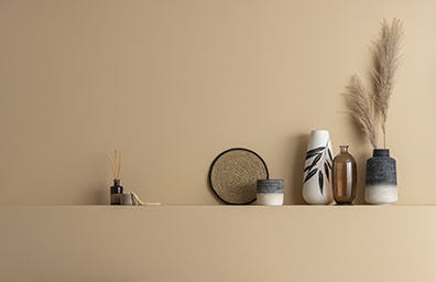 A neutral paint colour back-drop with black cane chair in foreground and small decorative accessories on shelf