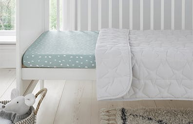 blue and white bedding in a cot turned cot bed