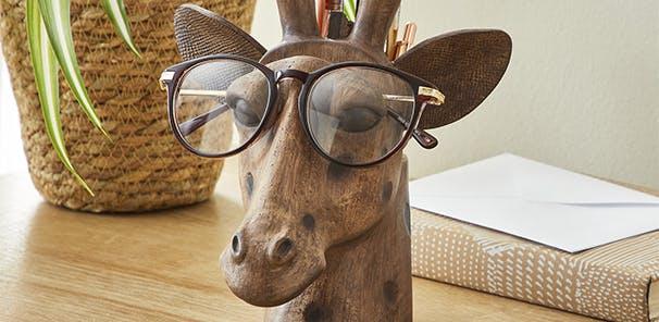 Giraffe pen pot and glasses holder on a sideboard