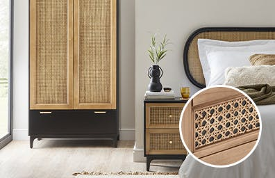 Rattan side table & wardrobe next to a bed covered in a white throw