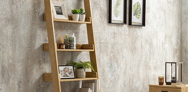Oak effect ladder shelf resting against a concrete effect wall with faux plants and pictures on it