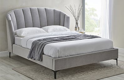 light grey upholstered bed with curved headboard in a neutral bedroom