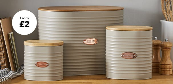 A collection of neutral ribbed design kitchen canisters on a worktop