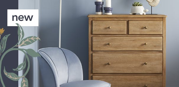 Light blue room with 5 drawer wooden chest & baby blue upholstered chair