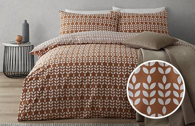 white leaf shaped marks on butterscotch background duvet cover in a neutral room