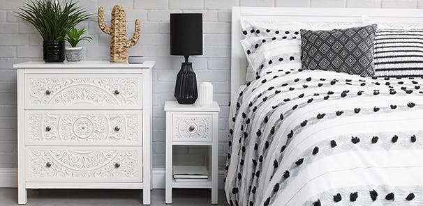 Bedroom with white furniture and monochrome bedding