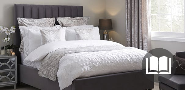 white bedding in a luxurious bedroom with grey and silver accents. Book icon on the image