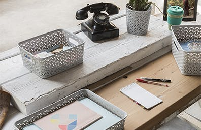 Grey paper trays sitting on a wooden desk surface