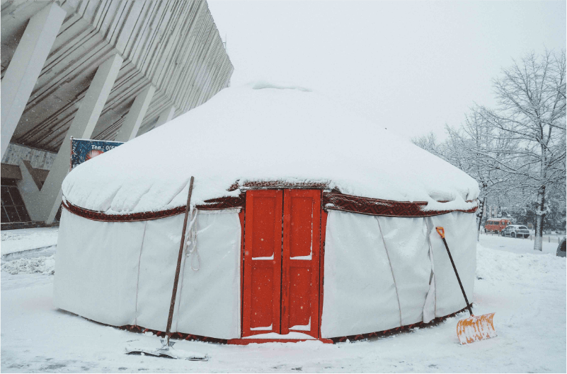 Yurt with red door in the snow