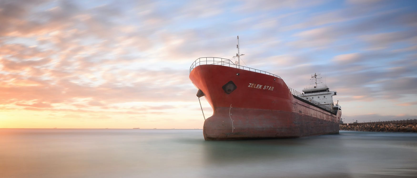A photograph of a cargo vessel stationary in a bay