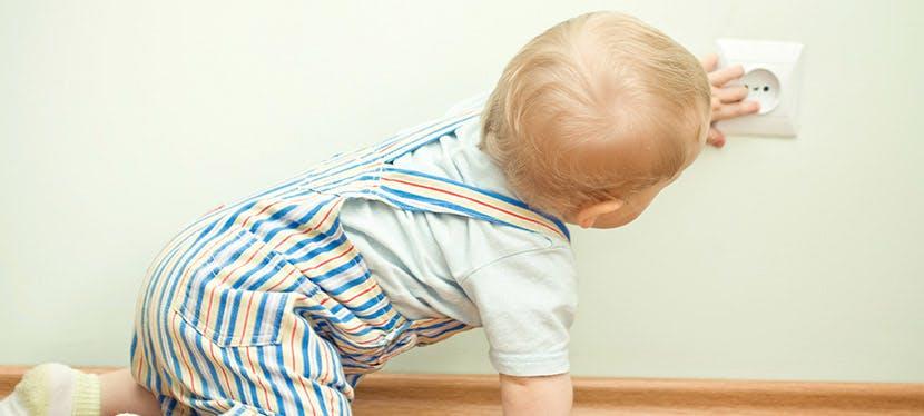 Un bébé qui essaye de mettre ses doigts dans une prise