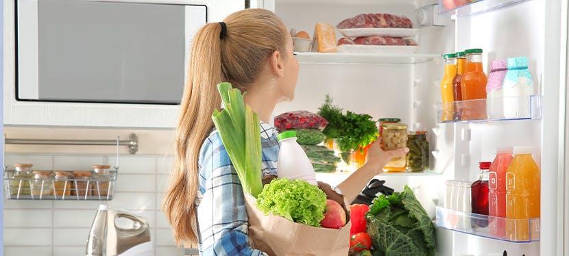 Une femme qui range son frigo