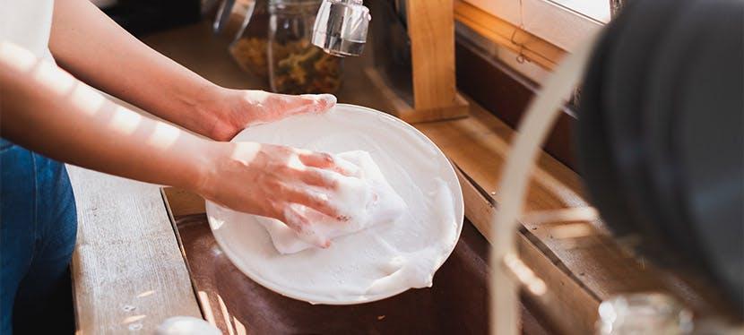 Une personne faisant la vaisselle le robinet d'eau fermé.