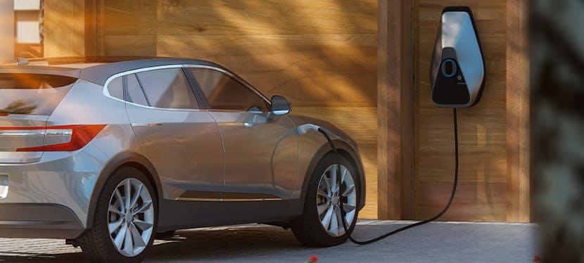 Une voiture électrique en train de charger dans une maison individuelle