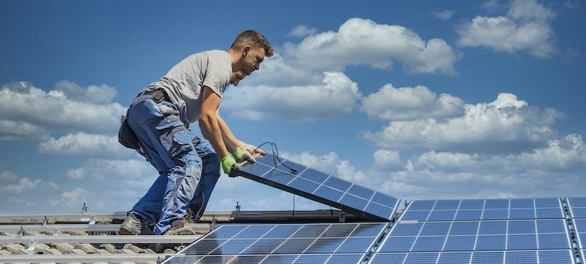 Deux hommes sont en train de procéder à l'installation de panneaux photovoltaïques