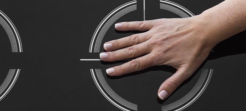 Une main posée sur une plaque à induction