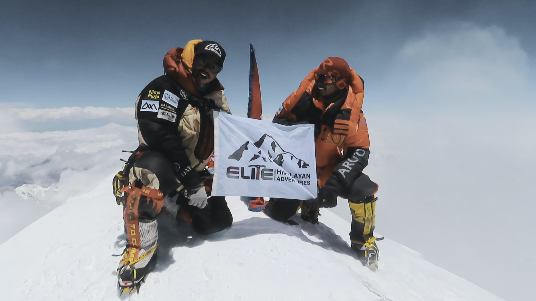 Nims and Mingma David proudly raising elite flag from the summit of Kanchenjunga