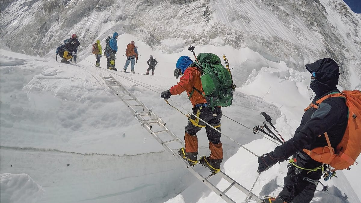 Expedition climbers crossing ladder on glacier