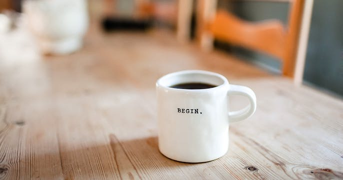 Coffee mug titled BEGIN on dining table to demonstrate it's time to start contracting