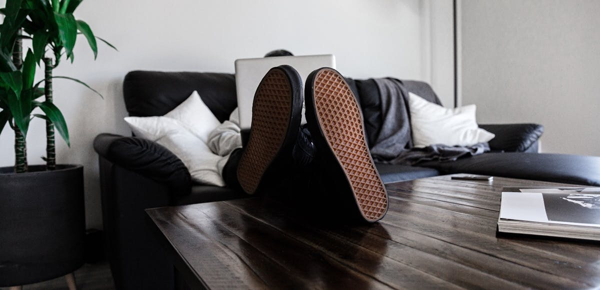 Man sitting on couch behind laptop with feet on the table