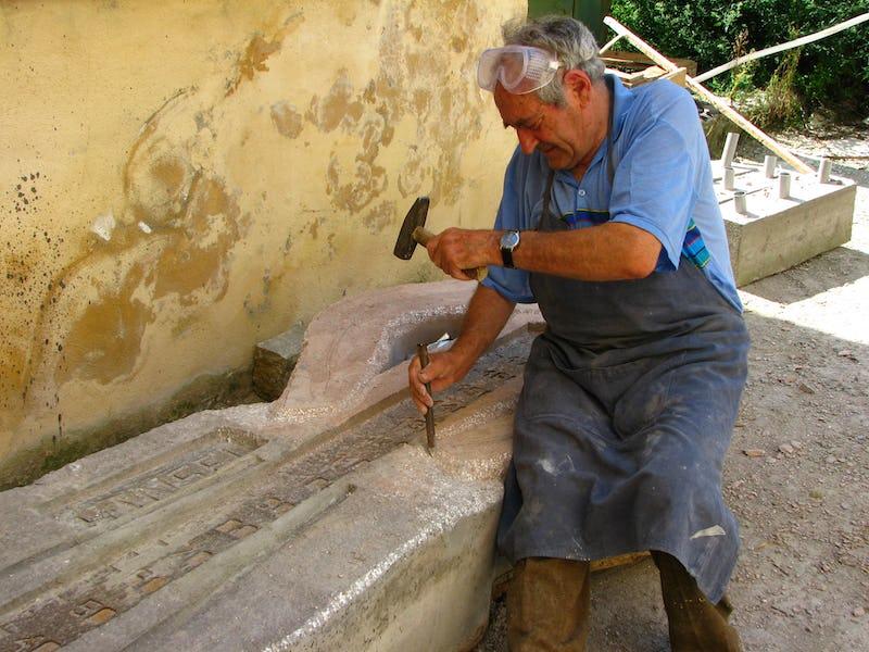 Emil Mureșan în timp ce sculptează în piatră
