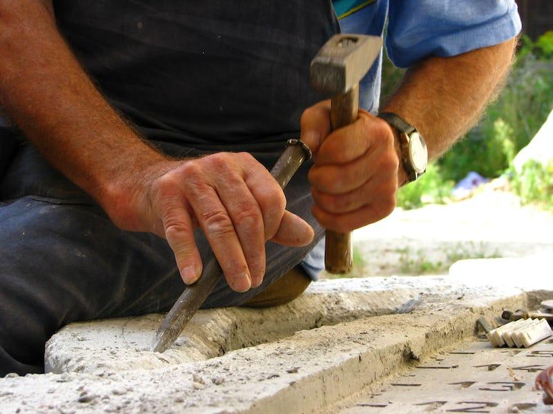 O daltă de dimensiune mare bătută cu un ciocan în piatră