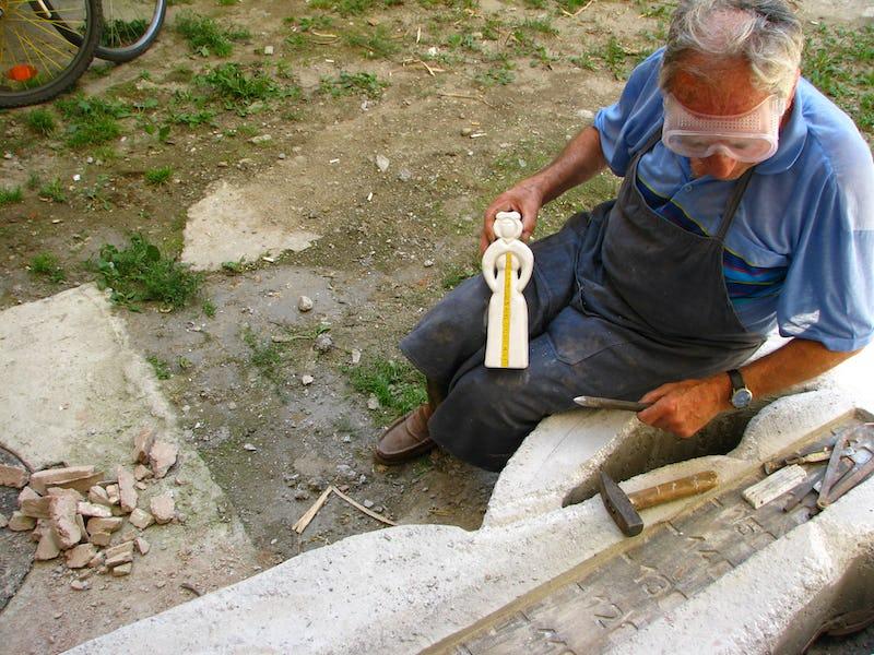 Emil Mureșan arată macheta unei lucrari sculptate în piatră