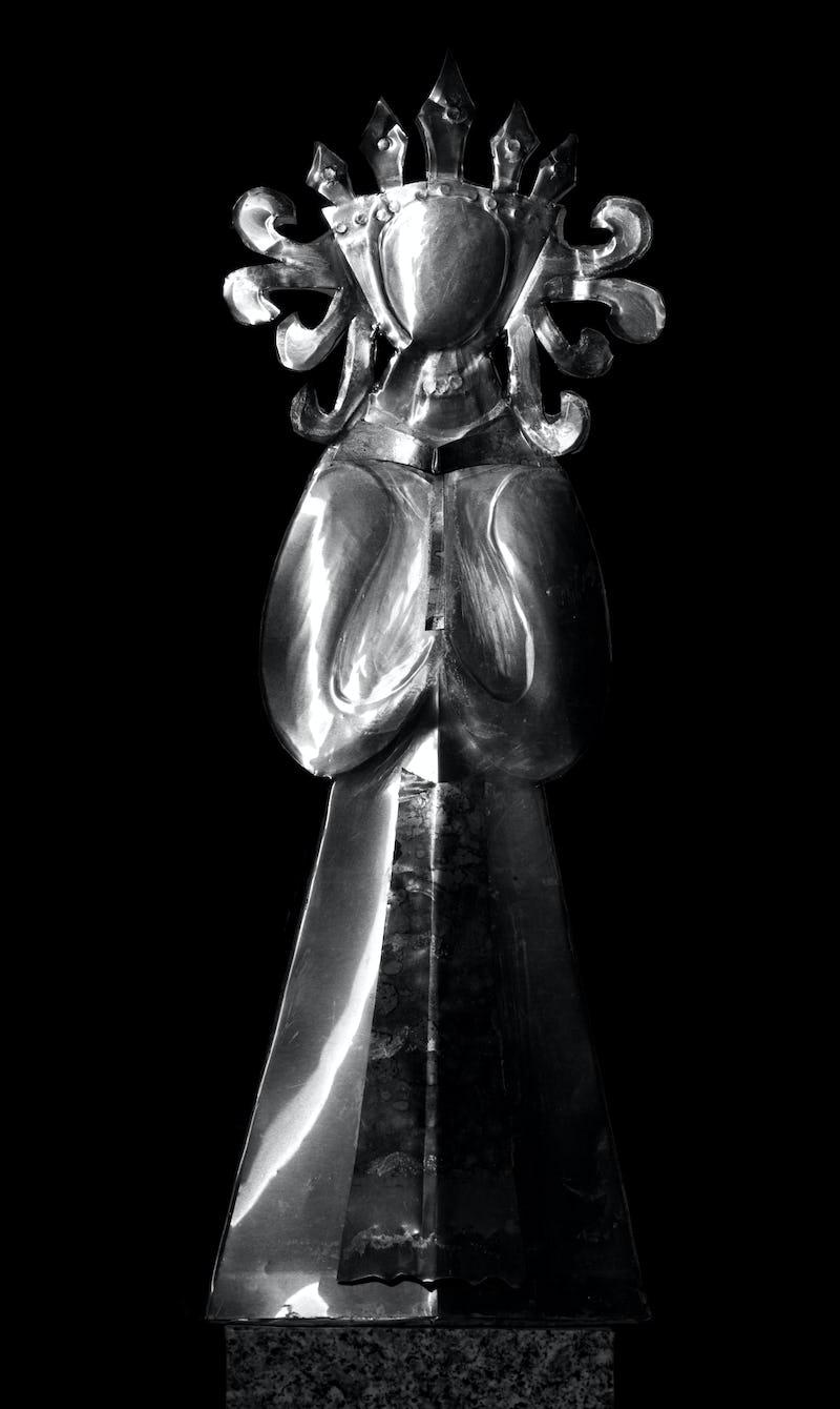 Lucrare din metal reprezentând o regină rugându-se