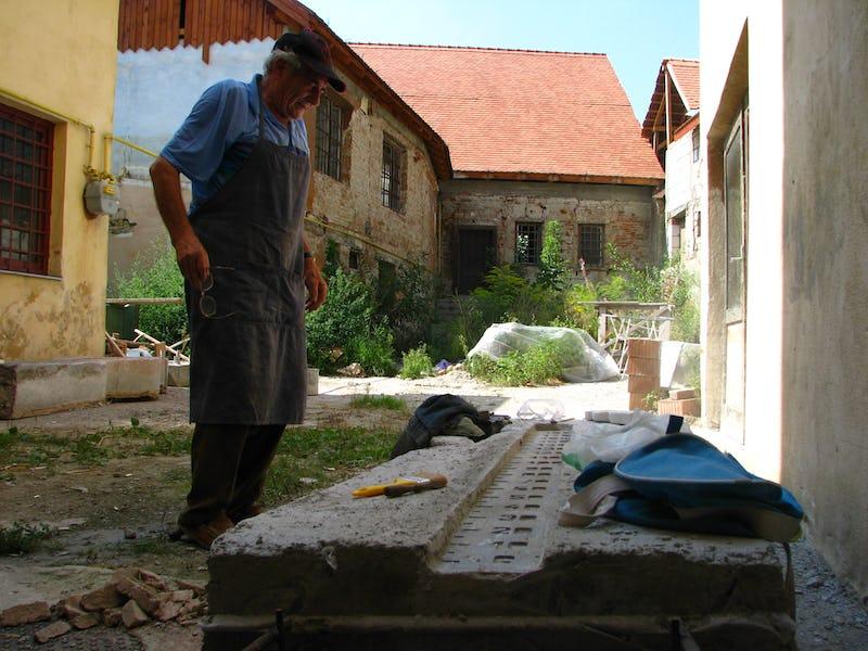 Emil Mureșan privind una dintre sculpturile sale în piatră
