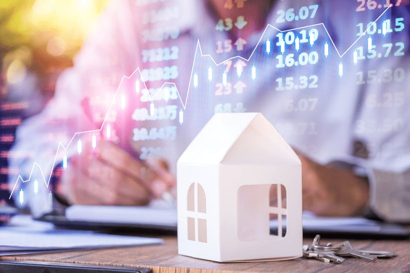 A picture of a small house and a stock market