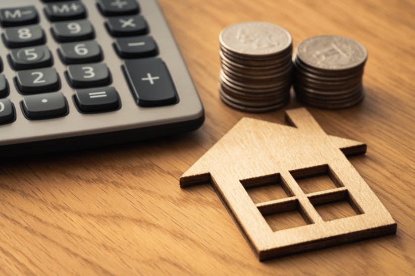 a wooden house, coins and calculator on a table