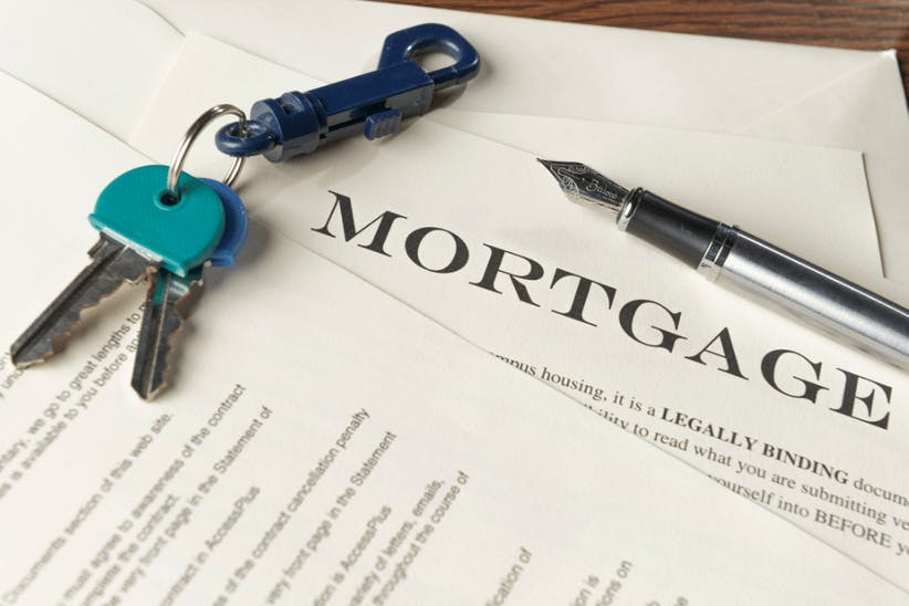 A picture of a keys and a mortgage contract
