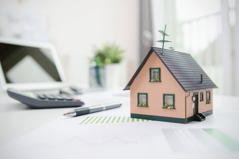 A picture of a caluclator, a pen and a wooden house
