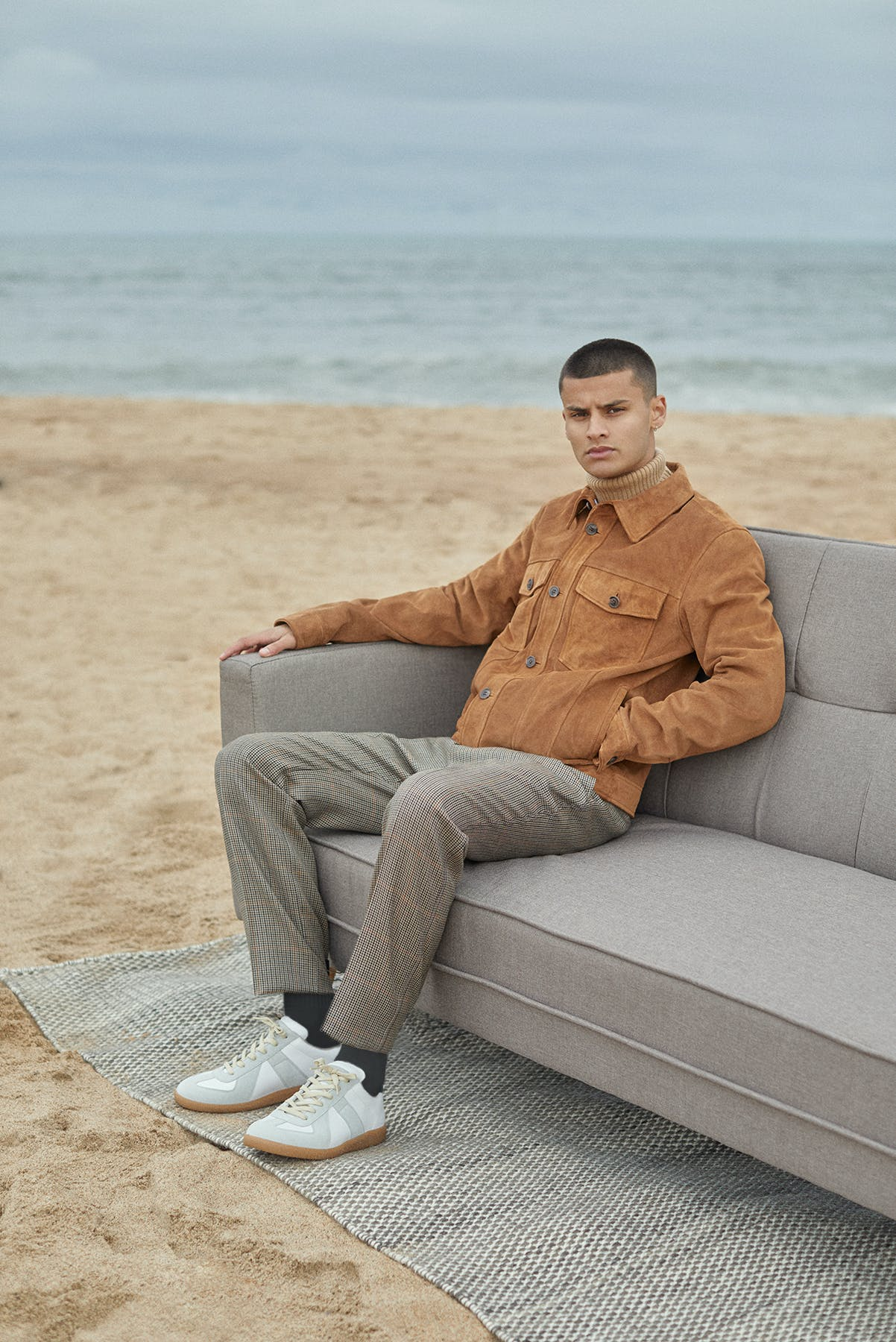 Suede A.P.C. jacket worn for Bare Minimum END. editorial on sofa at the beach